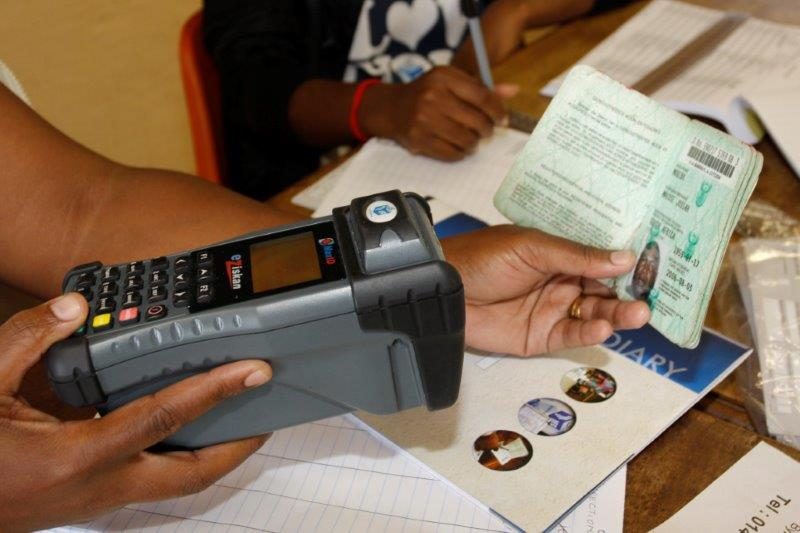 An IEC staff member uses the Zip-Zip to scan a voter's green-barcoded ID.