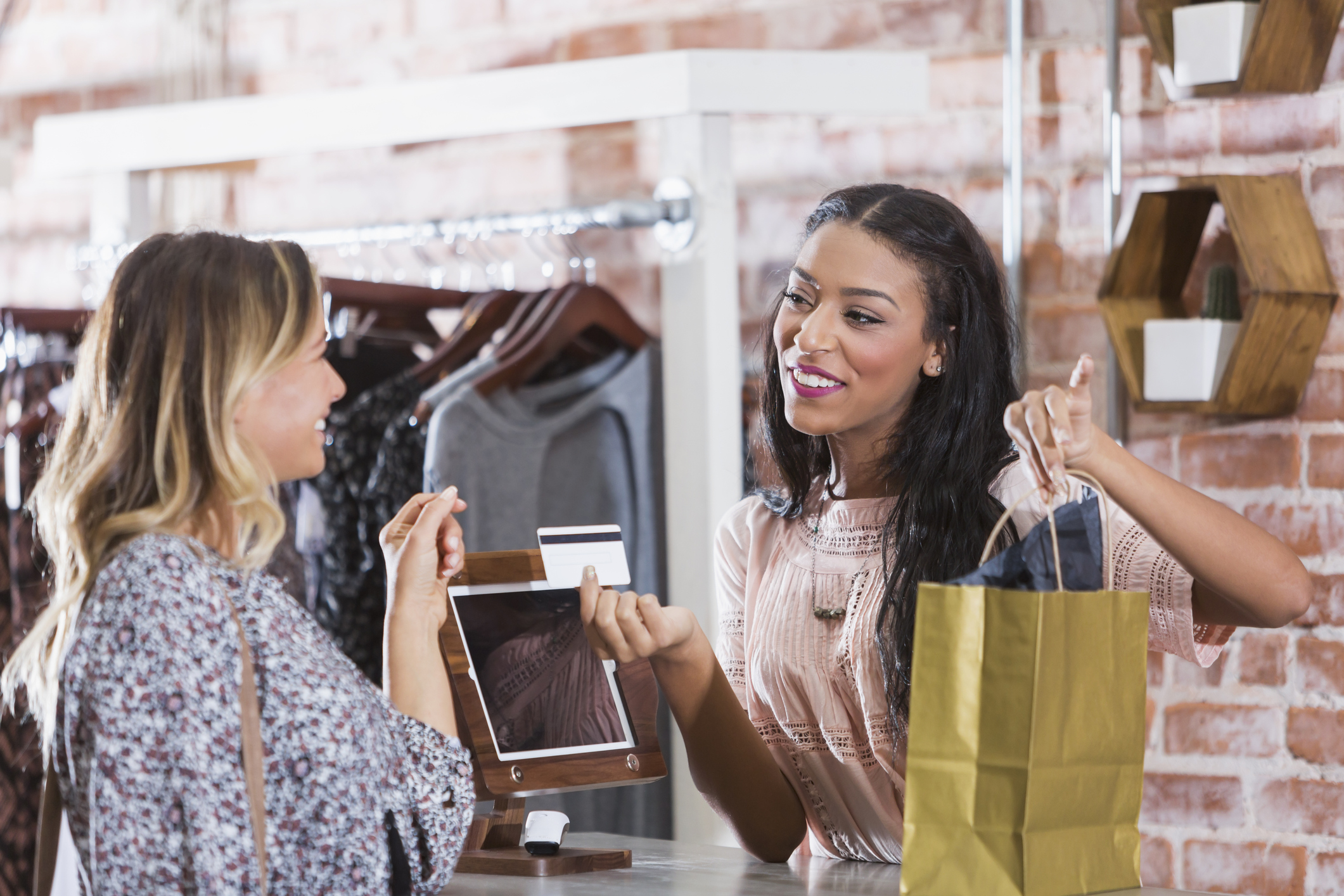 Image: iStock© - Cashier helping customer at checkout counter of store
